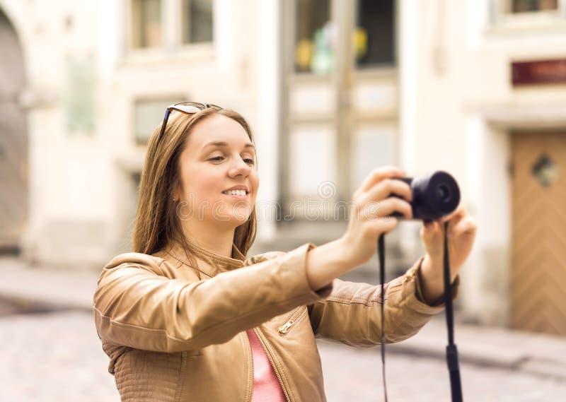 Donna sorridente che prende le foto con la macchina fotografica digitale immagini stock