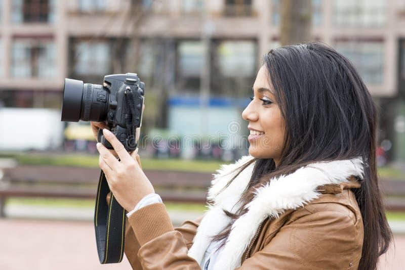 Donna sorridente che prende le immagini con la macchina fotografica nella via. fotografia stock