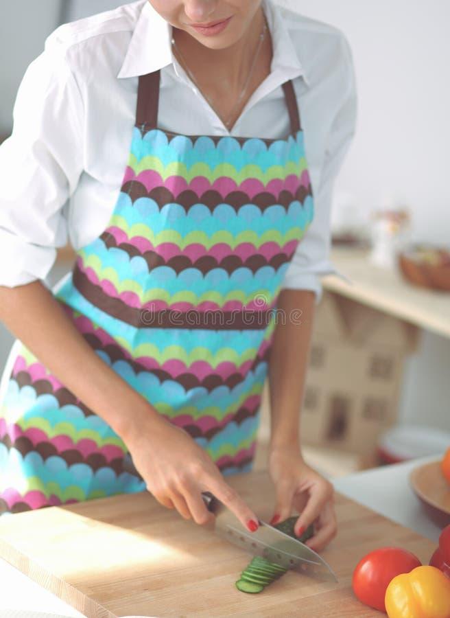 Donna sorridente che prepara insalata nella cucina fotografia stock