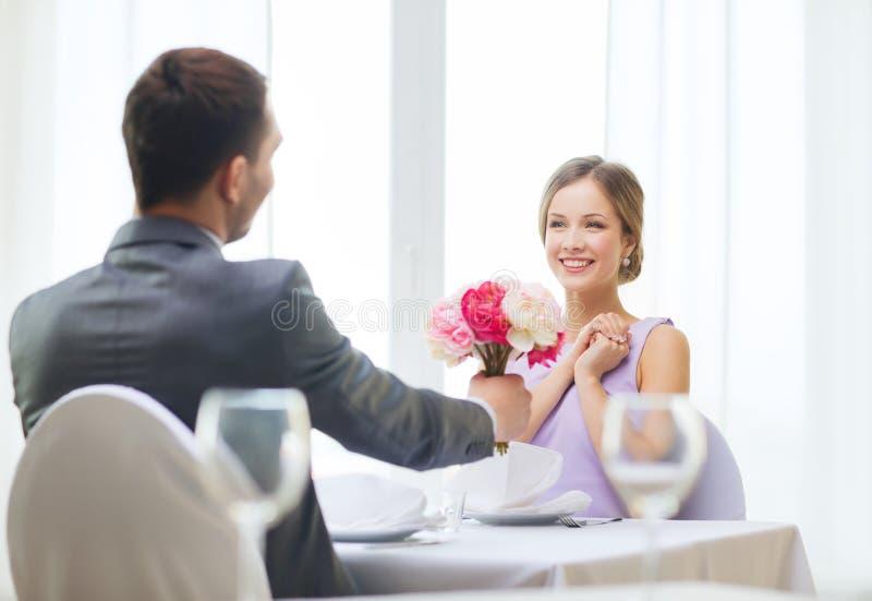 Donna sorridente che riceve mazzo dei fiori fotografia stock