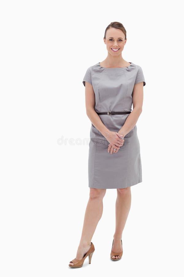 Donna sorridente che si leva in piedi in su e tenere le sue mani fotografie stock