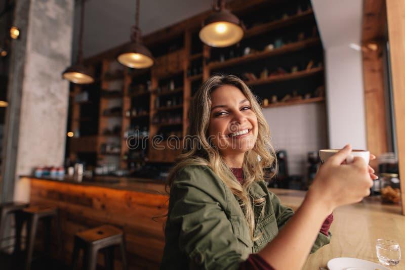 Donna sorridente che si siede al caffè con la tazza di caffè immagini stock