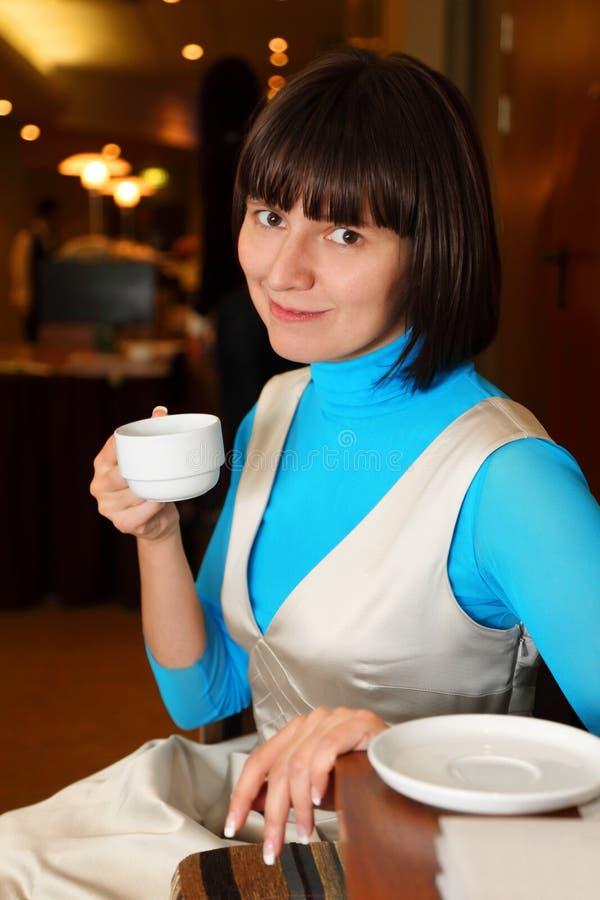 Donna sorridente che si siede in caffè con la tazza immagini stock libere da diritti