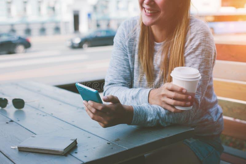 Donna sorridente che si siede in caffè della via e che legge l'alimentazione della rete sociale dentro il suo telefono cellulare immagine stock