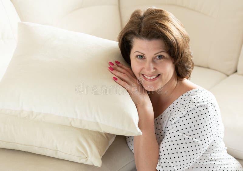 Donna sorridente che si siede con il cuscino dal sofà immagine stock
