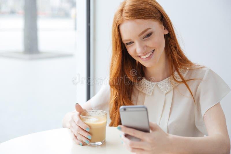 Donna sorridente che si siede nel caffè e nel per mezzo del telefono cellulare fotografia stock