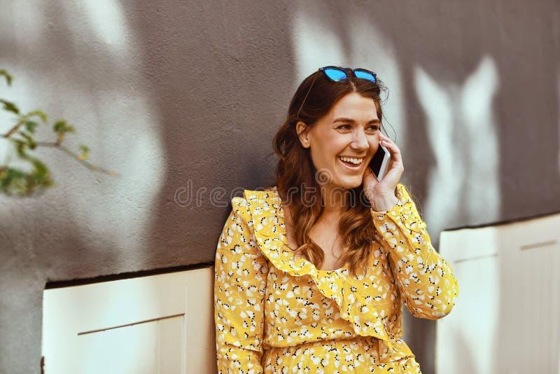 Donna sorridente che si siede nella città che parla sul suo cellulare immagini stock libere da diritti