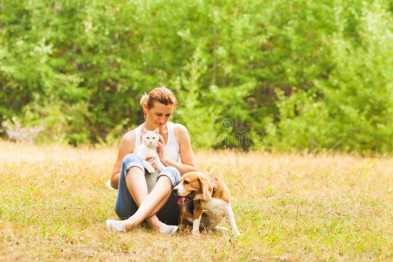 Donna sorridente che si siede su un'erba con il gatto ed il cane immagine stock