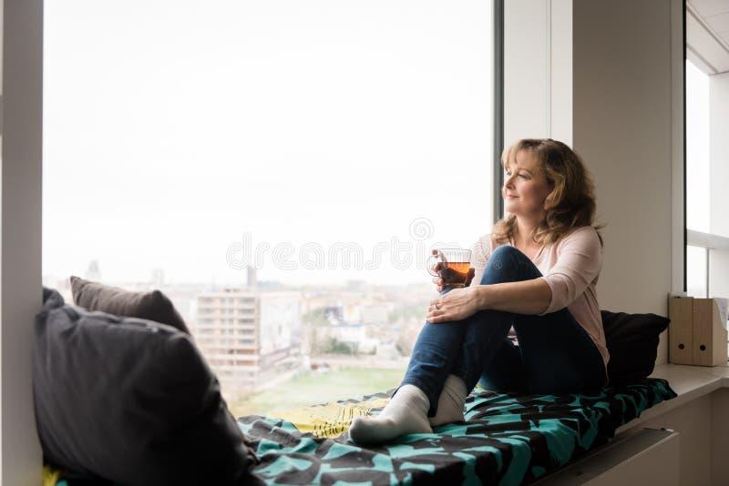 Donna sorridente che si siede vicino alla finestra e che guarda fuori immagini stock