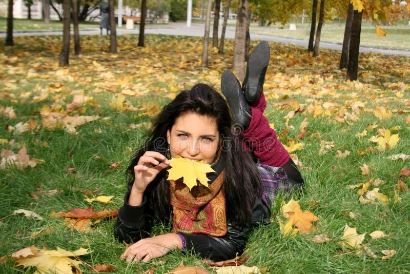 Donna sorridente che si trova su una moquette dei fogli fotografie stock libere da diritti