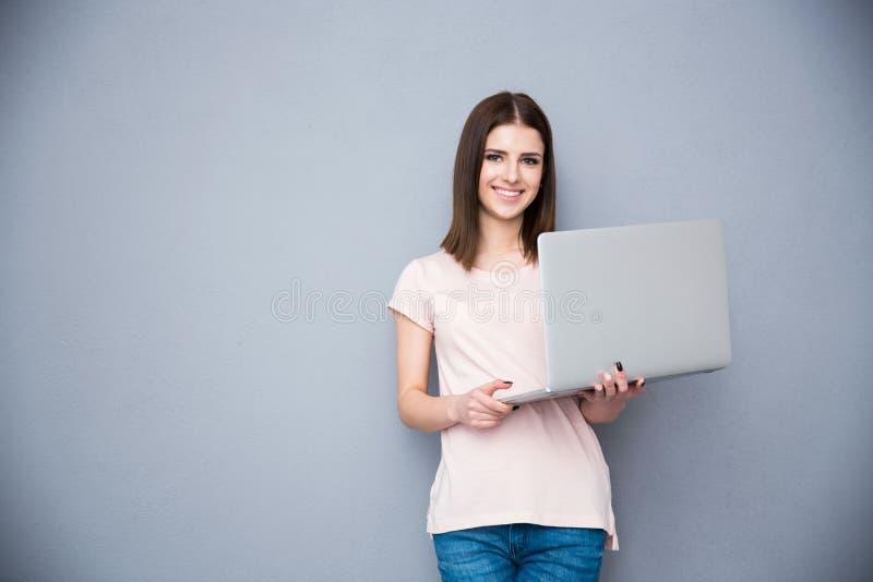 Donna sorridente che sta con il computer portatile immagini stock