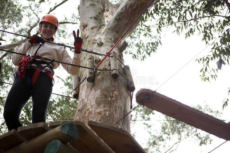 Donna sorridente che sta sulla piattaforma di legno che posa per la fotografia nella foresta fotografia stock