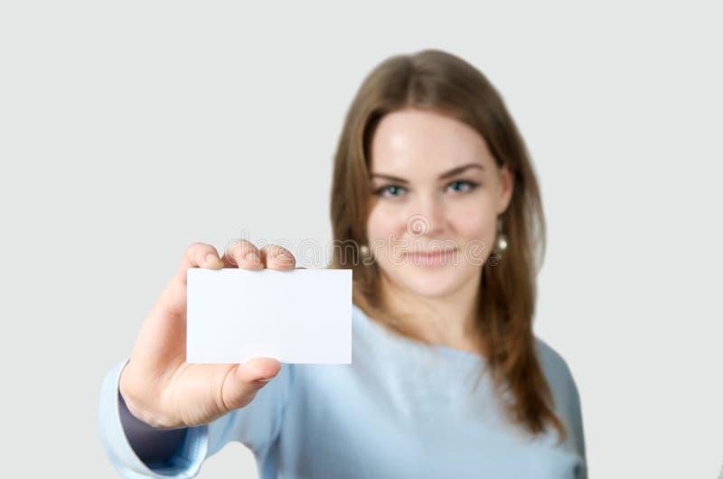 Donna sorridente che tiene biglietto da visita in bianco immagini stock