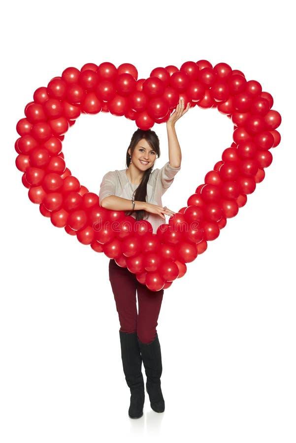 Donna sorridente che tiene il cuore rosso del pallone fotografia stock