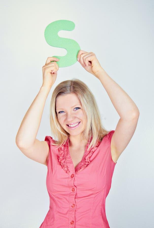 Donna sorridente che tiene la lettera S fotografia stock