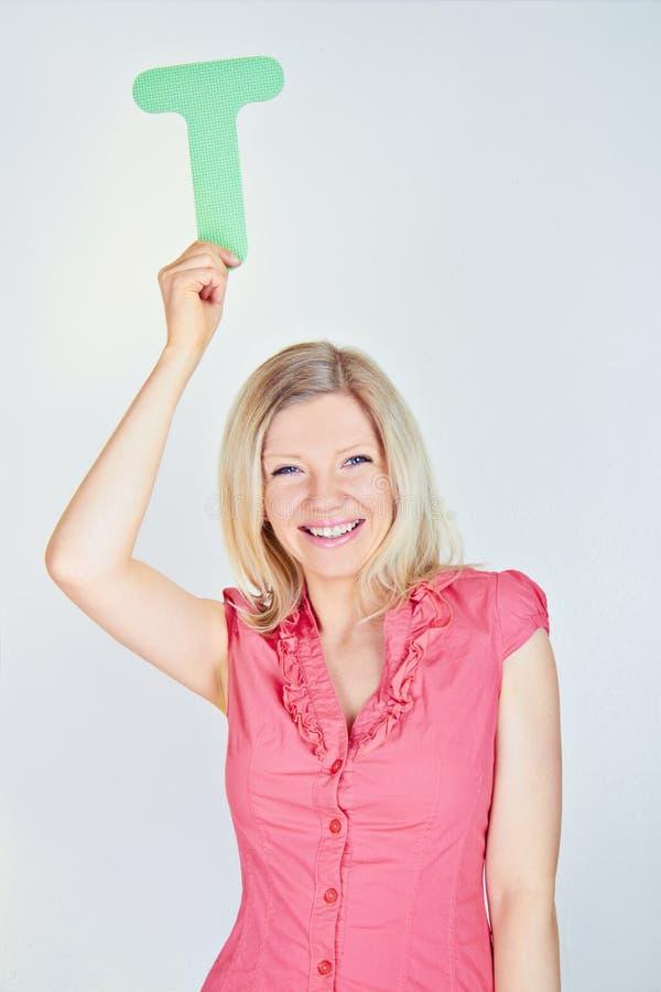 Donna sorridente che tiene la lettera T fotografia stock