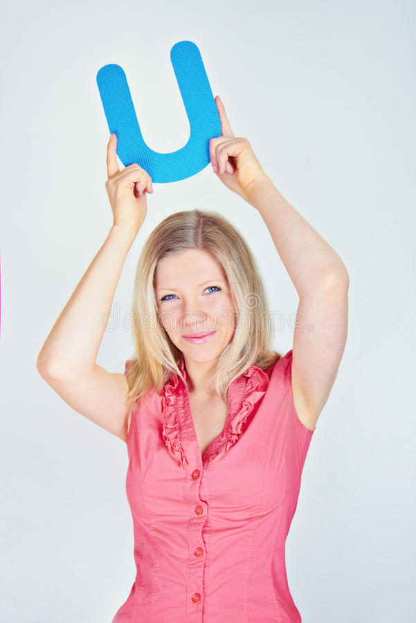 Donna sorridente che tiene la lettera U immagini stock libere da diritti