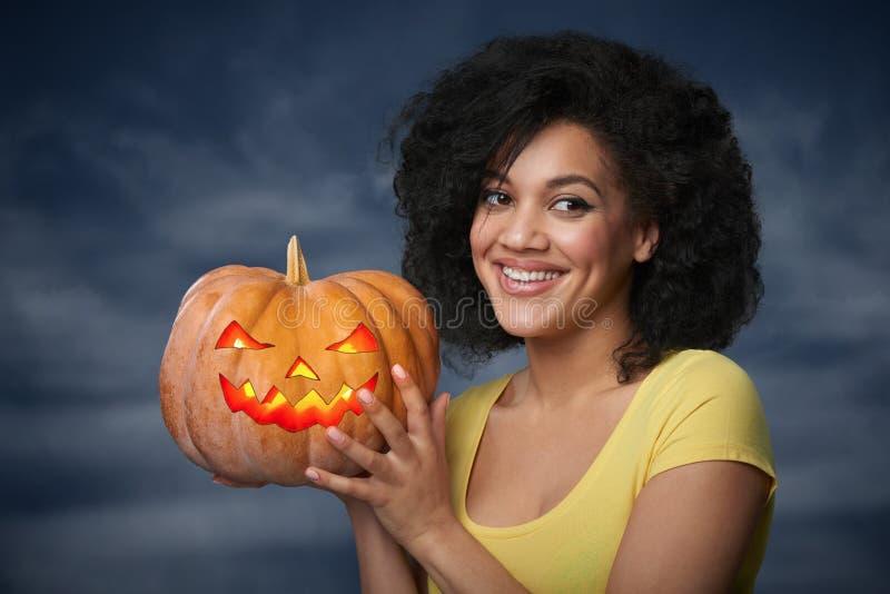 Donna sorridente che tiene la zucca di Halloween fotografie stock