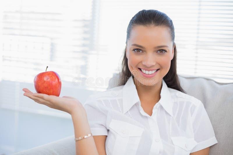 Donna sorridente che tiene mela rossa che esamina macchina fotografica fotografia stock libera da diritti