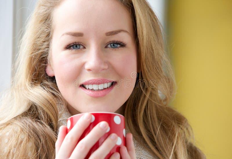 Donna sorridente che tiene tazza di tè immagine stock