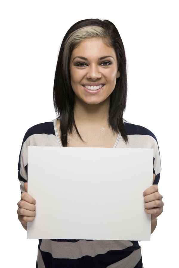 Donna sorridente che tiene un segno in bianco immagine stock libera da diritti