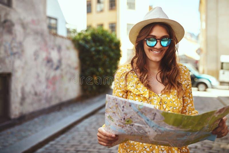 Donna sorridente che tiene una mappa mentre esplorando lo streptococco della città del ciottolo fotografia stock