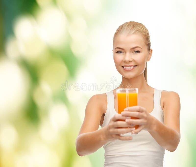Donna sorridente che tiene vetro di succo d'arancia fotografia stock