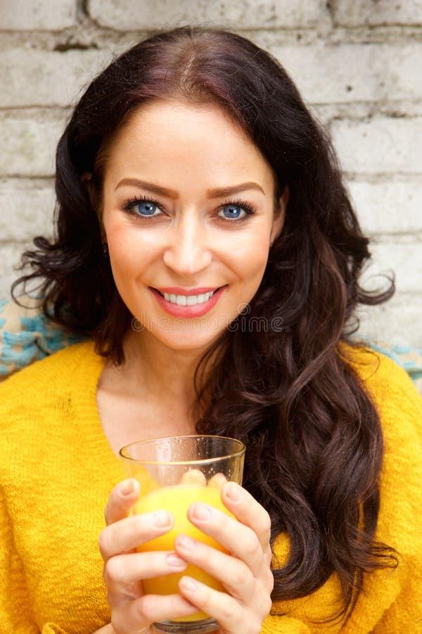 Donna sorridente che tiene vetro di succo d'arancia fotografie stock libere da diritti