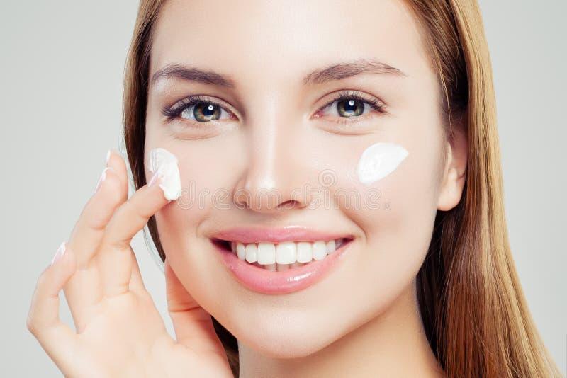 Donna sorridente con chiara pelle che applica crema d'idratazione, bello primo piano femminile del fronte Skincare, bellezza e tr immagini stock