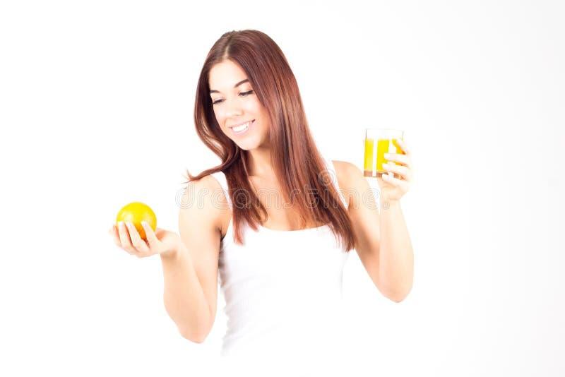 Donna sorridente con i denti bianchi che giudicano arancio ed il vetro di succo d'arancia Alimento sano fotografie stock
