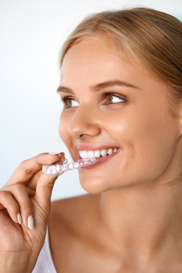 Donna sorridente con il bello sorriso facendo uso dell'istruttore invisibile dei denti immagini stock libere da diritti