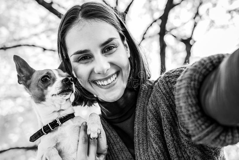 Donna sorridente con il cane all'aperto in autunno che fa selfie fotografie stock libere da diritti