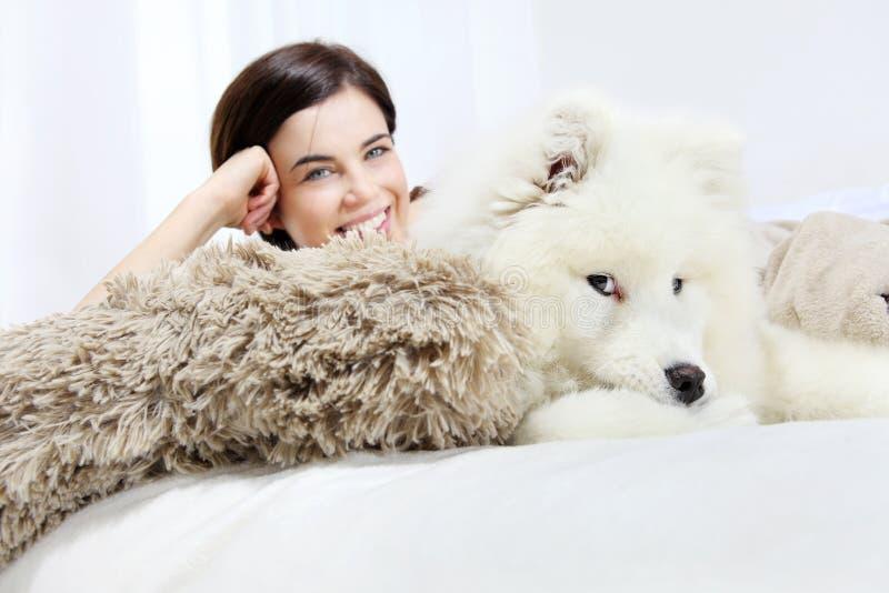 Donna sorridente con il cane di animale domestico immagini stock