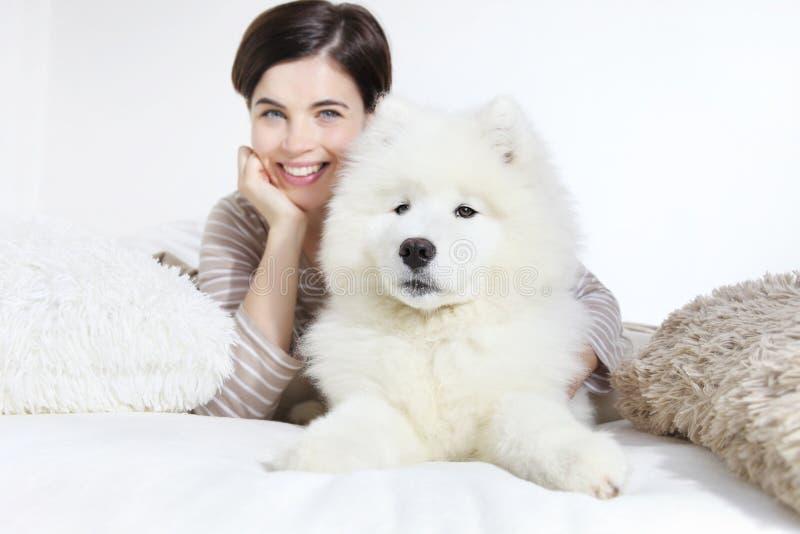 Donna sorridente con il cane di animale domestico fotografie stock
