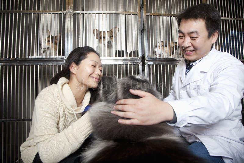 Donna sorridente con il cane di animale domestico ed il veterinario fotografia stock libera da diritti
