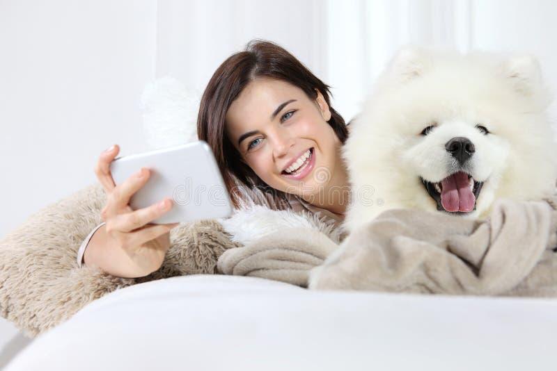 Donna sorridente con il cane di animale domestico Selfie immagini stock