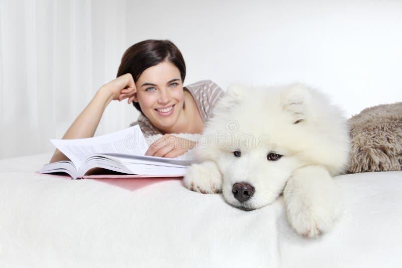 Donna sorridente con il cane ed il libro di animale domestico immagine stock libera da diritti