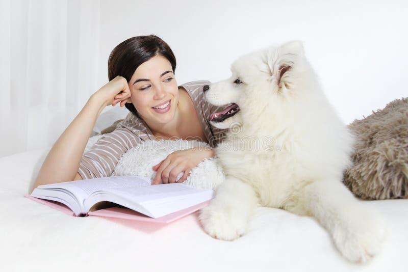 Donna sorridente con il cane ed il libro di animale domestico immagini stock libere da diritti