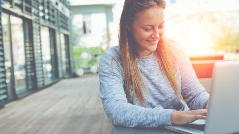 Donna sorridente con il computer portatile che si siede in caffè della via, navigando web e l'alimentazione della rete sociale, m fotografie stock