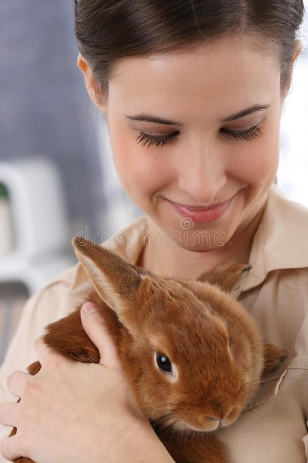 Donna sorridente con il coniglio dell'animale domestico fotografia stock