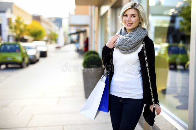 Donna sorridente con il deposito dell'esterno dei sacchetti della spesa e della borsa fotografie stock libere da diritti