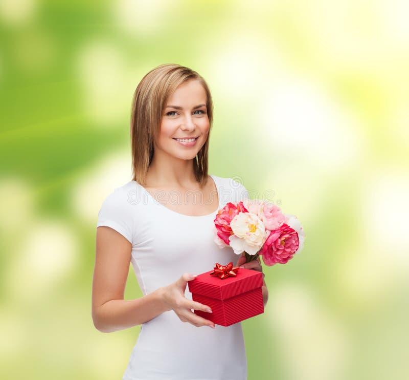 Donna sorridente con il mazzo dei fiori e del contenitore di regalo immagini stock libere da diritti