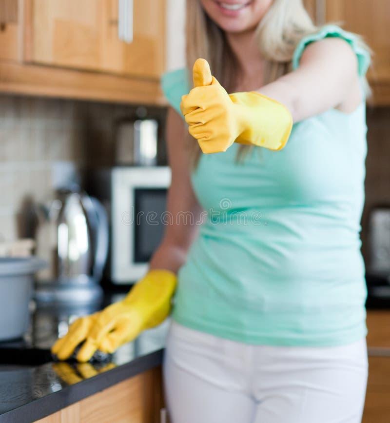 Donna sorridente con il pollice sulla pulitura della cucina fotografia stock