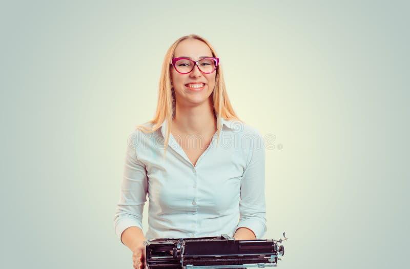 Donna sorridente con la macchina da scrivere antiquata immagini stock