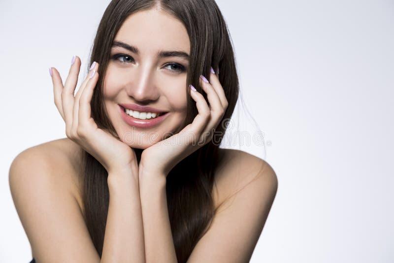 Donna sorridente con la testa sulle mani fotografie stock