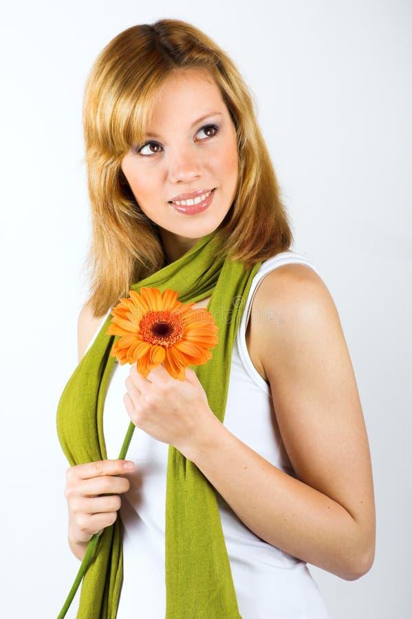 Donna sorridente con un fiore fotografie stock
