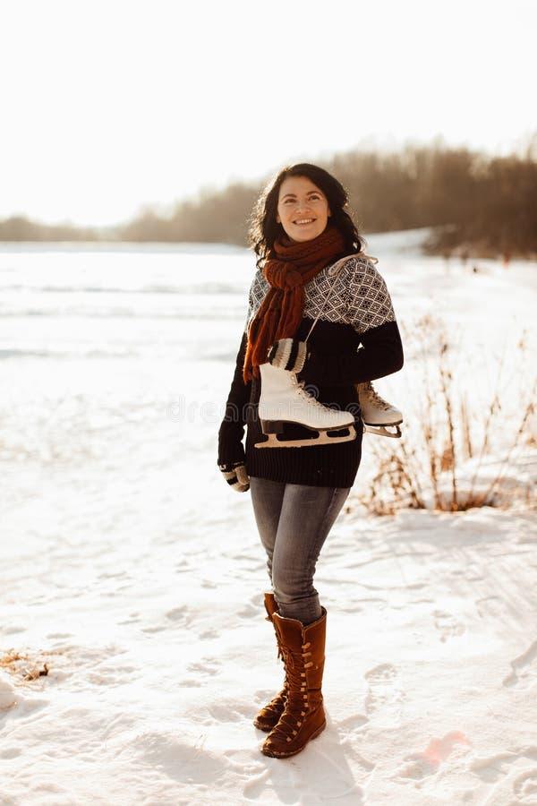 Donna sorridente con un paio dei pattini da ghiaccio legati insieme sopra una spalla fotografia stock libera da diritti