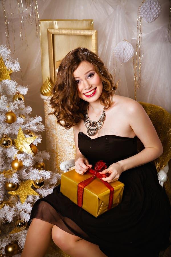 Donna sorridente con un regalo in sue mani fotografia stock libera da diritti