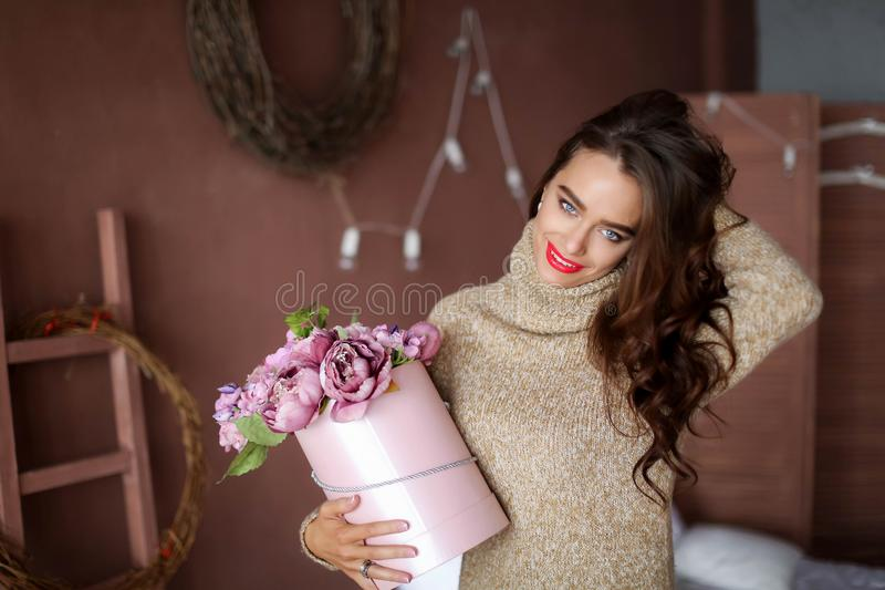Donna sorridente in contenitore di regalo della tenuta del pigiama ed esaminare la macchina fotografica, concetto di giorno di bi immagine stock libera da diritti