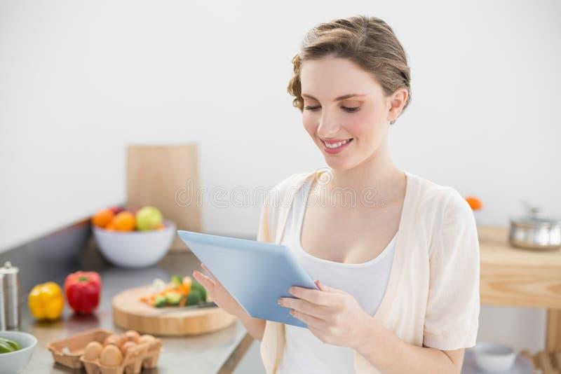 Donna sorridente contenta che lavora con la sua compressa in cucina fotografia stock libera da diritti